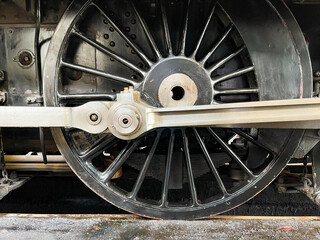 Closeup view of the driving wheels and connecting rods on a vintage steam locomotive. No people.