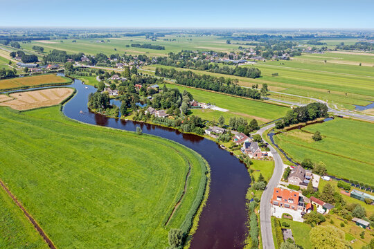 Aerial from a traditional dutch landscape: A little river, houses and flat land in the Netherlands
