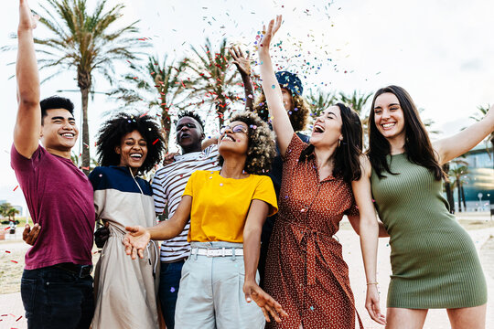 Young multiracial hipster people having fun in summer party celebration - Group of young friends laughing and celebrating all together while throwing coloured confetti at weekend event outdoors