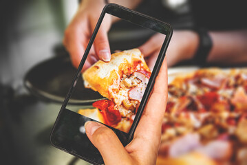 woman hand holding and showing smart phone takes a photo woman Hand takes a slice of meat Pizza with Mozzarella cheese, salami, Tomatoes, pepper, ham, Spices and chicken in cafe. food photos