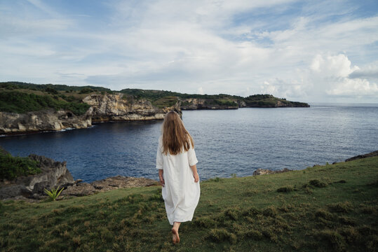 young woman in white dress goes to cliff on the ocean. High quality photo