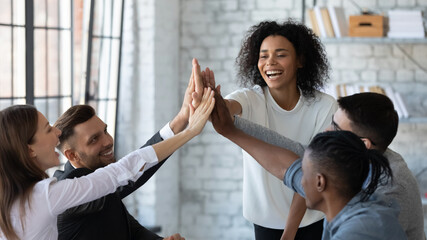 Fototapeta Overjoyed young multiracial businesspeople join hands give high five celebrate shared victory or win in office. Smiling millennial diverse employees engaged in teambuilding activity. Success concept. obraz