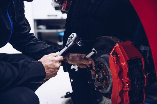 Man car mechanic repairing car brakes in car service