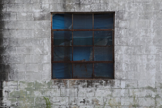 old window in wall with blue behind glass