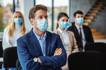 Obraz Group of business people with face masks sitting on seminar during corona virus. Selective focus on man in foreground. - fototapety do salonu