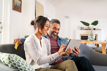 Multiethnic mid adult couple using digital tablet at home