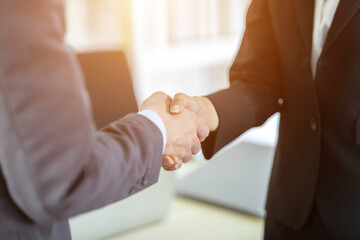 Fototapeta businesswoman and businessman shaking hands at In the office room background after the contract is signed or handshake greeting deal,business expressed confidence embolden and successful concept obraz