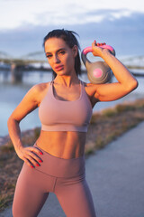 Young woman holding kettlebell on shoulder at riverside