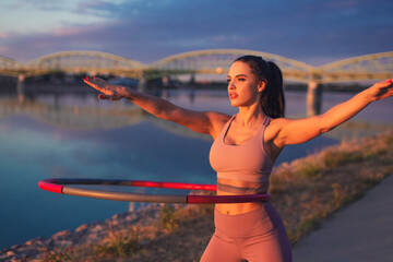 Young woman doing hula hoop exercise at riverside