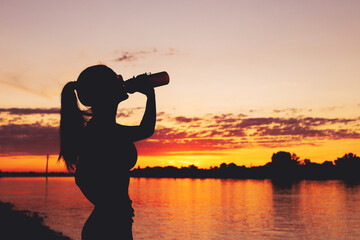 Woman silhouette drinking from bottle after workout in sunset