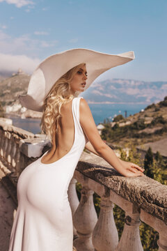 beautiful woman with blond hair in elegant white dress posing on balcony with sea view