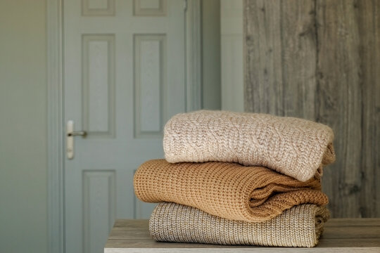 Stack of clean freshly laundered, neatly folded clothes on bedroom dresser's top. Pile of different sweaters of pastel colors. Copy space, close up, background.