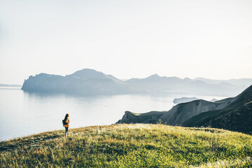 Woman backpacker with black bag walks along green meadow on mountainous coastline landscape against calm sea water and rocky cliff in morning mist