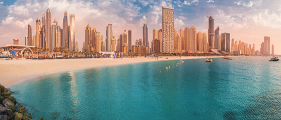 Cityscape panorama of the golden sand illuminated by the setting sun in the JBR beach area. Amazing skyscrapers and azure waters of the Persian Gulf are waiting for visitors