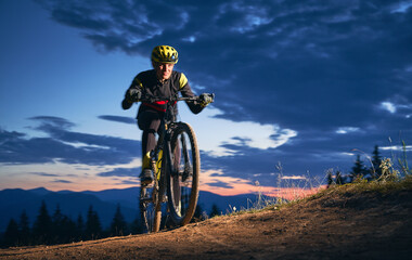 Motion blur of young man cyclist riding his bicycle in the mountains in dusk. Cyclist wearing helmet and uniform traveling in wild nature. Horizontal snapshot. Concept of extreme sport.