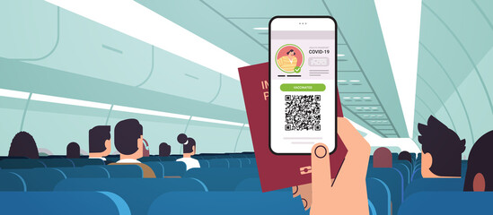 passenger hand holding digital vaccinate certificate and global immunity passport in airplane coronavirus immunity