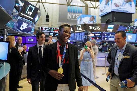 Ashleigh Johnson, Goalkeeper for the U.S. Olympic Women's Water Polo Team walks the trading floor before ringing the opening bell at the New York Stock Exchange (NYSE) in Manhattan, New York City