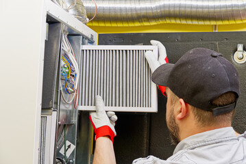 Fototapeta HVAC service technician changing dirty air filter in the central ventilation system. Change filter in rotary heat exchanger recuperator. Air duct ventilation system maintenance for clean air. obraz