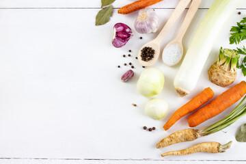 Warzywa i przyprawy na białym tle. Składniki bulionu warzywnego. Potrawy wegetariańskie, zdrowe, ekologiczne jedzenie