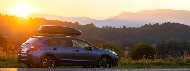 SUV car with roof rack luggage container for off road travelling parked at roadside at sunset.