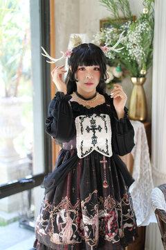 Portrait of asian girl in lolita fashion dress in vintage garden background