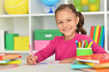 Porait of cute girl drawing picture at home