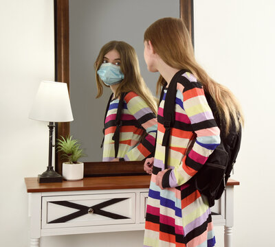 Student Unmasked Looking in Mirror