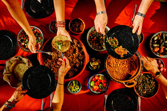 Overhead shot of a dinner table with Mexican food and hands. Tacos, beans, carnitas, habanero, salsa