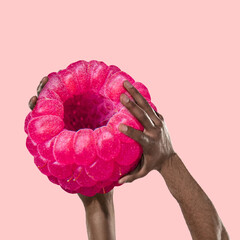 Composition with huge raspberry and human strong hands holding it. Healthy eating concept. Art collage