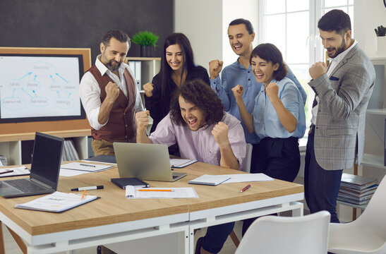 Happy business team celebrating successful deal or project completion. Group of excited teammates standing near office table, looking at laptop computer screen, fist pumping and shouting Yes we did it