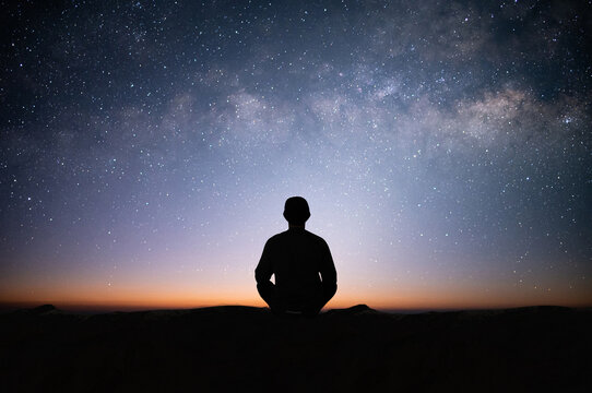 Silhouette of young traveler sitting and meditating with the star and milky way alone on top of the mountain. He enjoyed traveling and was successful when he reached the summit.