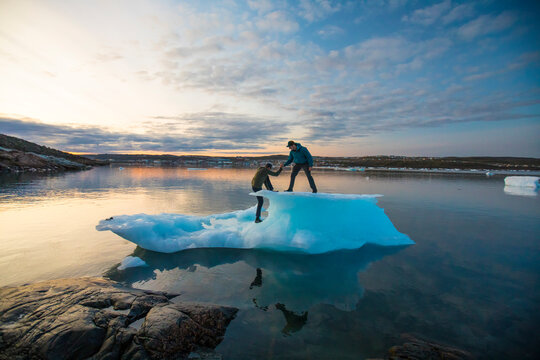 Friends help one another on to an iceberg.