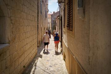Toeristen in een smal steegje in de oude stad Krk op het eiland met dezelfde naam in Kroatië op een hete zomerdag