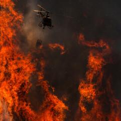 Brandweerhelikopter die de hel bestrijdt in een bosbrand.