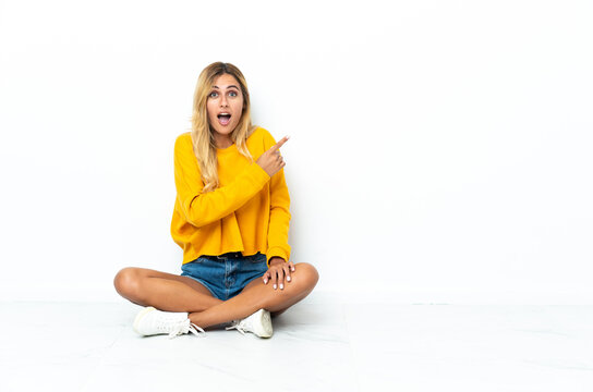 Young blonde Uruguayan woman sitting on the floor isolated on white background surprised and pointing side