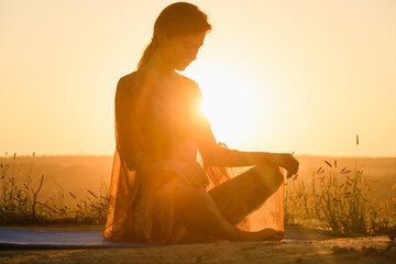 Beautiful girl sit in yoga lotus pose against sun in warm light, wear transparent cloth, meditation and stretching outdoors
