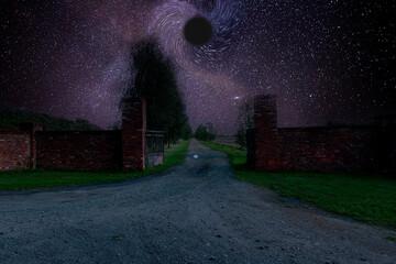 Brama za którą jest długo polna droga. Jest noc, niebo jest rozgwieżdżone, w centralnym miejscu jest wizualizacja czarnej dziury.