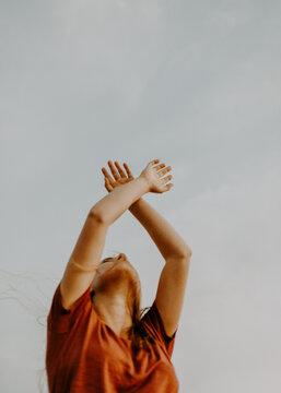 Vertical shot of a young, cute blond woman posing in a beautiful, dancing way