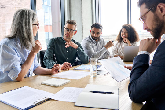 Diverse international executive business partners group discuss report at boardroom meeting table. Multiracial team negotiating project developing business strategy doing paperwork analysis in office.