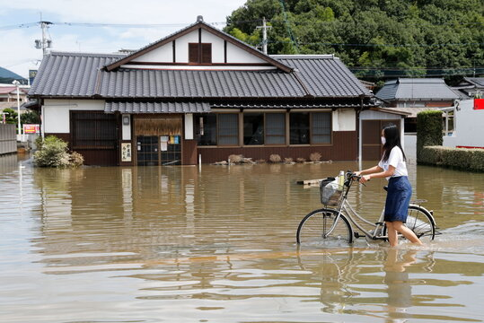 A woman pushes a bicycle through a flooded street in Takeo, Saga Prefecture, western Japan