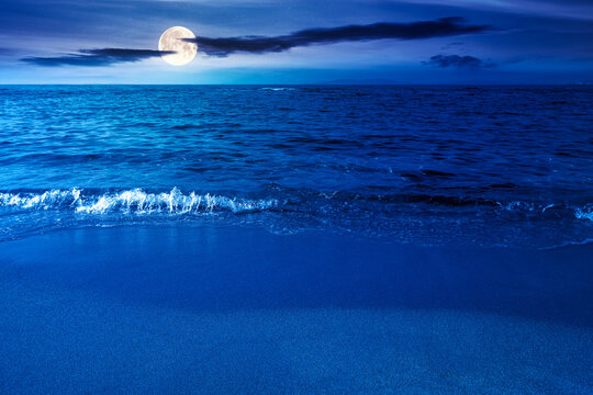 calm morning scenery at the sea. empty sandy beach in full moon light. relax and summer vacation concept. clouds on the sky at night