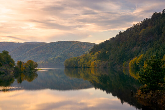 beautiful evening scenery with lake. glowing clouds reflecting on the water surface. wonderful autumnal landscape in mountains of romania