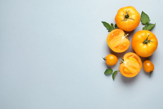 Cut and whole ripe yellow tomatoes with leaves on light background, flat lay. Space for text