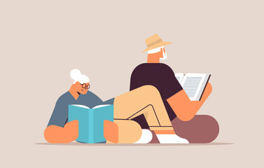 Obraz senior couple reading books old man and woman family spending time together relaxation retirement concept - fototapety do salonu