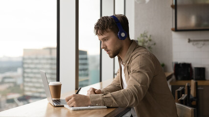 Young man listens audio course through wireless headphones takes notes makes assignment prepares for university exams, gain new knowledge, e-learns language use laptop video call and tutor assistance