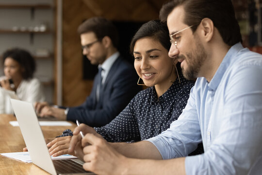 In modern office diverse colleagues Indian businesswoman and caucasian businessman workmates talking sit at desk coworking space use laptop, discuss work result, new business professional application