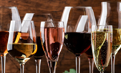 Fototapeta Wine tasting. Red, white, rose and champagne - still and sparkling wines sin glasses on vintage wooden table background obraz