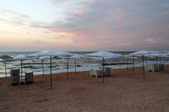Uncrowded beach area with sun loungers and parasols.