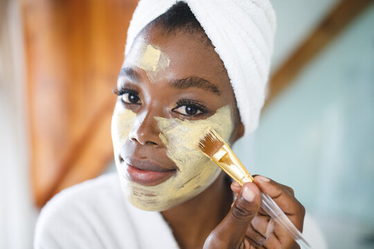 Portrait of smiling african american woman in bathroom applying beauty face mask