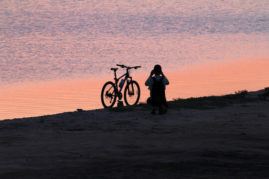 Man beside the bike takes a picture of the sunset near the water
